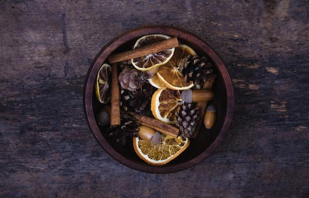 Tangerinas, cones, especiarias em um fundo de madeira. à época do ano novo e do natal, o natal bebe vinho quente. vista plana leiga, superior. bandeira