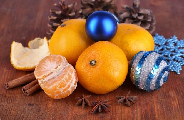 Tangerinas de natal e brinquedos de natal em close-up de mesa de madeira
