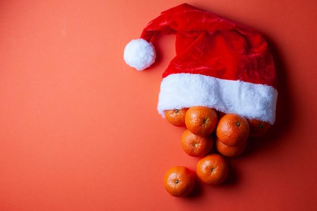 Tangerinas de natal em um chapéu de papai noel em um fundo laranja