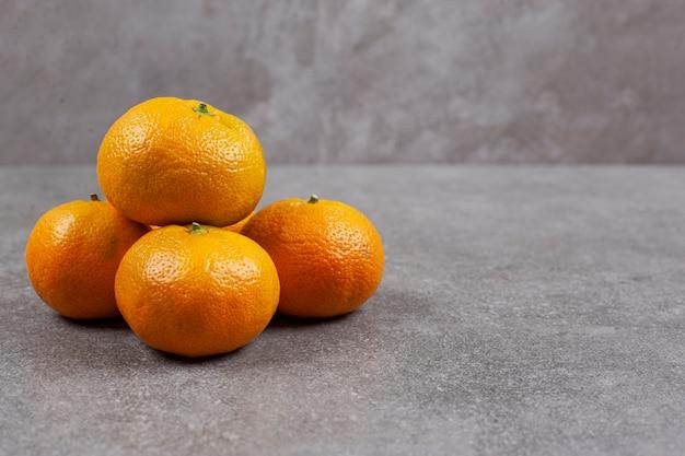 Tangerinas doces e frescas em uma superfície cinza
