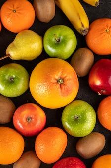 Tangerinas e kiwis frutas de cores diferentes, como maçãs verdes, peras e laranjas em um cinza