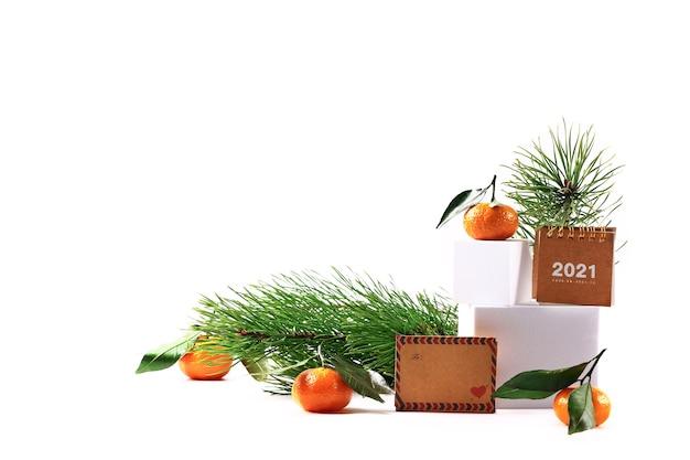 Tangerinas e um ramo de abeto, um calendário 2021 e uma carta em um fundo branco. concerto de natal minimalista e criativo na escandinávia