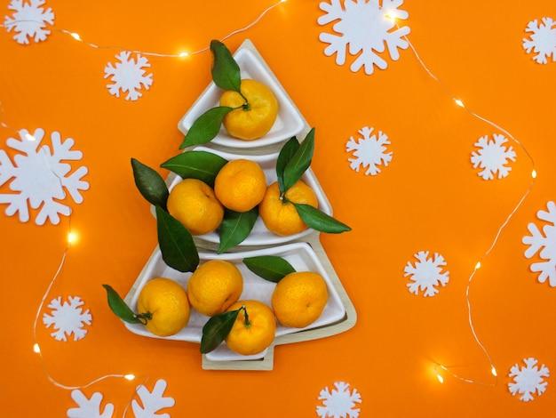 Tangerinas em forma de árvore de natal em um fundo laranja com flocos de neve decorativos brancos. fundo de comida de natal, vista de cima