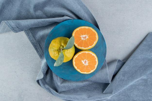 Tangerinas em um quadro azul em um pedaço de tecido, em mármore