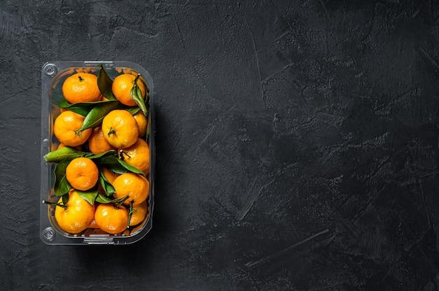 Tangerinas em um recipiente de plástico do supermercado. fundo preto. vista do topo. espaço para texto