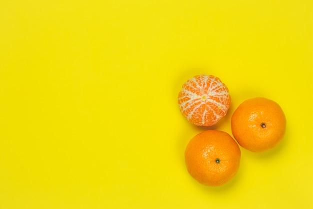 Tangerinas em uma parede de papel amarelo. quadro brilhante com tangerinas, copie o espaço para o texto. modelo, padrão. vista superior das frutas cítricas. conceito de humor de verão divertido.