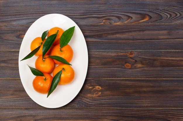 Tangerinas em uma placa. ainda vida com tangerinas na mesa de madeira