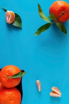 Tangerinas em uma superfície azul ao lado de fatias de tangerina.