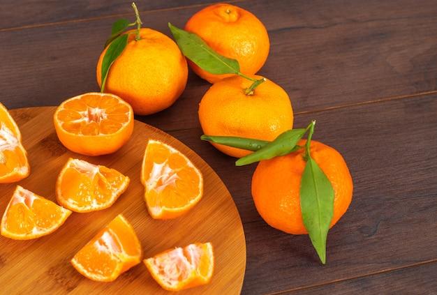 Tangerinas fatiadas na tábua com tangerinas inteiras na mesa de madeira