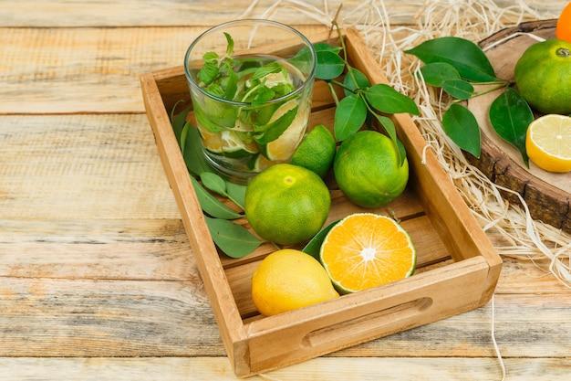 Tangerinas, folhas e água desintoxicante em uma caixa de madeira com tangerinas na mesa de madeira