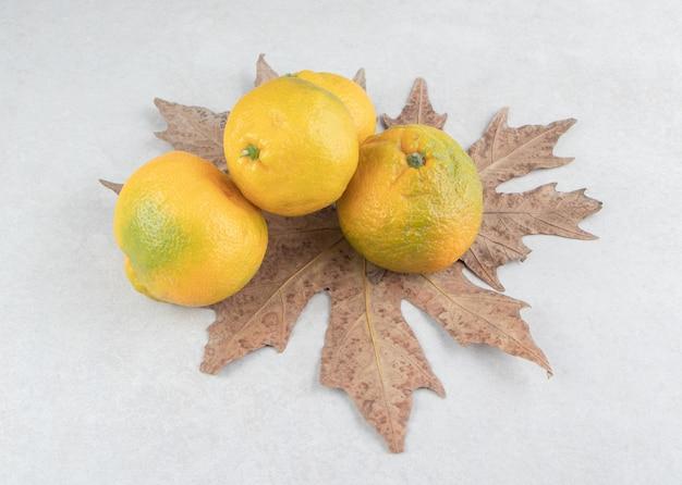 Tangerinas frescas com folhas secas na mesa branca.