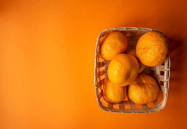 Tangerinas frescas de laranja em uma cesta em um fundo laranja