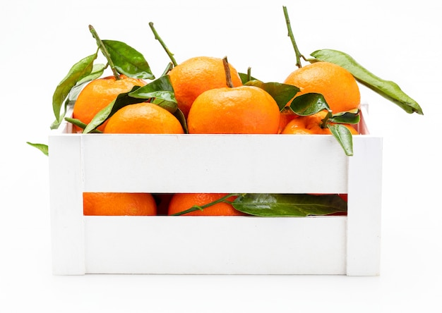 Tangerinas frescas e cruas com folhas verdes em caixa de madeira