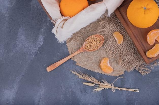Tangerinas frescas em caixa de madeira e fatias de tangerinas na serapilheira.