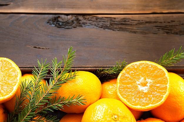 Tangerinas frescas em caixa marrom com fundo de madeira com ramos verdes de pinheiro