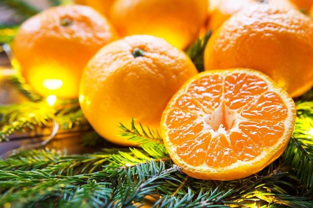 Tangerinas frescas em luzes de guirlanda, em galhos de pinheiro e enfeites - o fundo brilhante de ano novo. metade de uma laranja, aroma cítrico do feriado. natal, ano novo. espaço para texto.