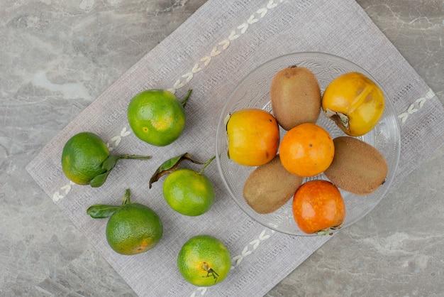 Tangerinas frescas, kiwis e caquis na toalha de mesa.