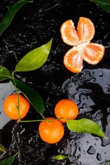 Tangerinas frescas laranja descascada e cortada em um fundo preto, fundo cítrico, molhado