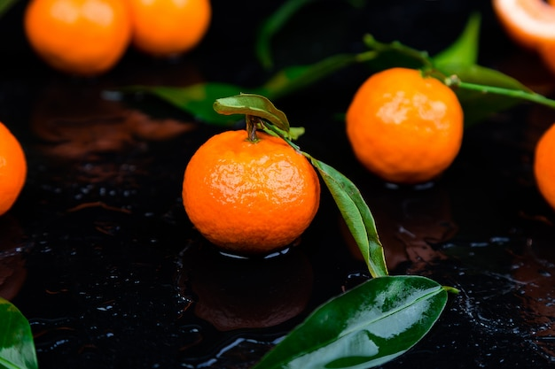 Tangerinas frescas laranja descascada e fatiada em um preto