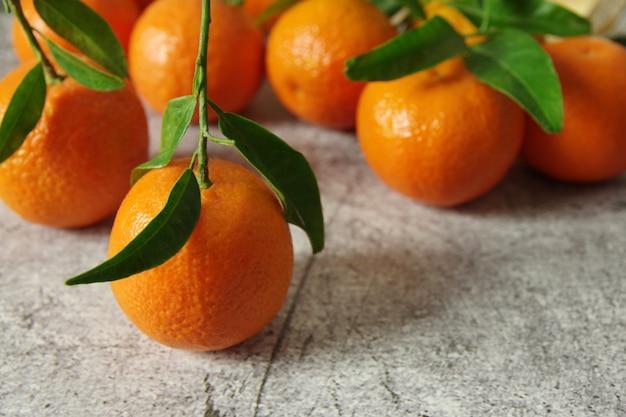 Tangerinas frescas perfumadas com folhas verdes em cima da mesa. tangerinas maduras e suculentas.