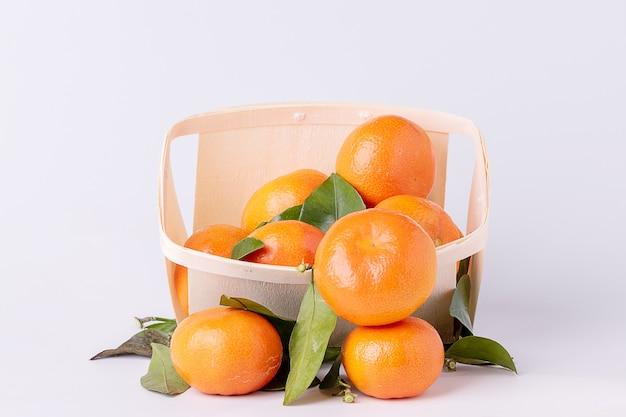 Tangerinas frescas, tangerinas, com folhas, num cesto de madeira com superfície branca.