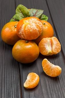 Tangerinas inteiras, fatias de tangerina descascadas.