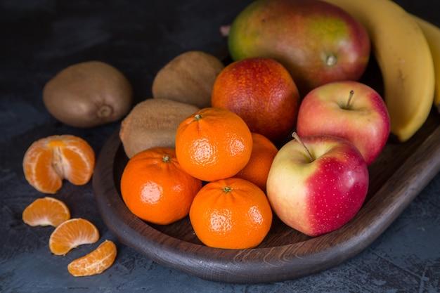 Tangerinas laranja banana manga e kiwi em uma mesa escura. alimentação saudável rica em vitaminas e fibras Foto Premium