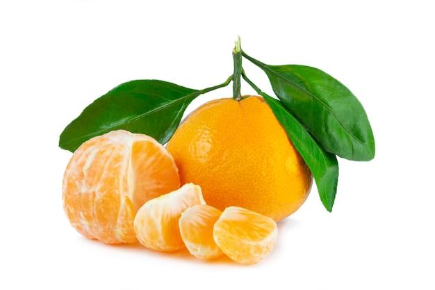Tangerinas laranja com folhas verdes e fatias descascadas