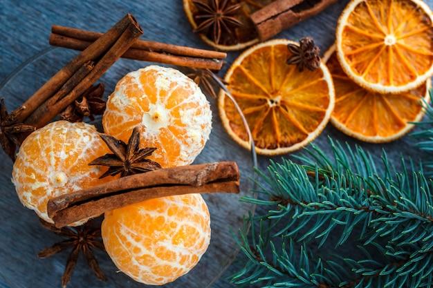 Tangerinas, laranjas secas, anis e paus de canela em uma mesa de madeira