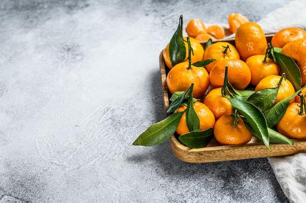 Tangerinas (laranjas, tangerinas, clementinas, frutas cítricas) com folhas em uma tigela de madeira. fundo cinza. vista do topo. espaço para texto