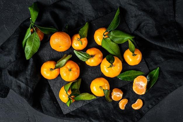Tangerinas (laranjas, tangerinas, clementinas, frutas cítricas) com folhas. fundo preto. vista do topo