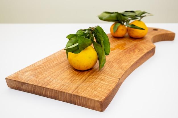 Tangerinas, laranjas, tangerinas, clementinas, frutas cítricas, com folhas no fundo de madeira rústica, espaço de cópia. satsuma de tangerina laranja fresco e tangerina no fundo cinza, configuração plana.