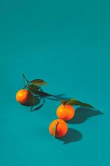 Tangerinas maduras brilhantes com sombras duras em um fundo turquesa