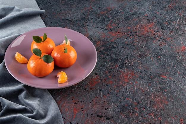 Tangerinas maduras com folhas colocadas em um prato roxo