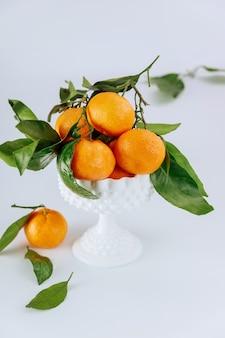 Tangerinas maduras e doces da flórida com folhas verdes em uma tigela.