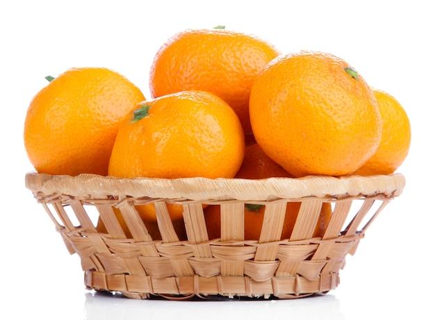 Tangerinas maduras e doces em uma cesta de vime, isoladas no branco