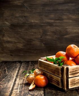 Tangerinas maduras em uma velha caixa em um fundo de madeira