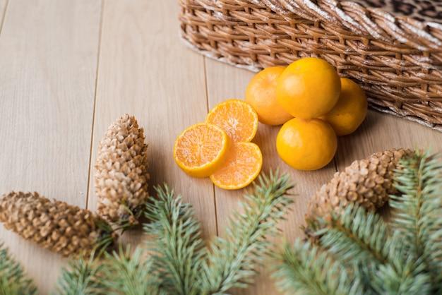 Tangerinas, mandarinas com galhos de árvore de natal em fundo de madeira. copie o espaço.