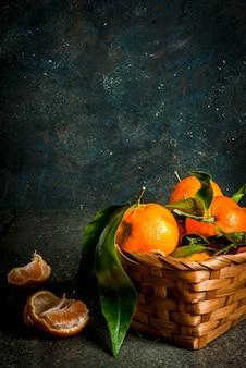 Tangerinas orgânicas cruas frescas com folhas verdes em pequena cesta no fundo escuro de pedra concreto, cópia espaço