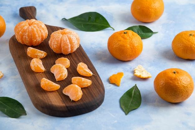 Tangerinas orgânicas descascadas ao lado de tangerinas inteiras