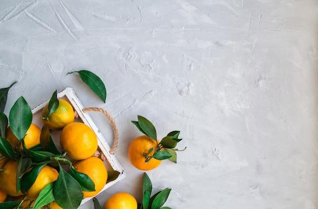 Tangerinas orgânicas frescas com folhas em uma bandeja de madeira branca em um fundo de concreto claro. vista superior