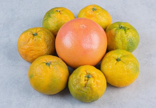 Tangerinas orgânicas (laranjas, clementinas, frutas cítricas) sobre fundo cinza.