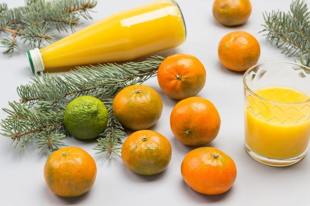 Tangerinas, suco de frutas cítricas em vidro e garrafa. ramos de abeto. vista do topo.