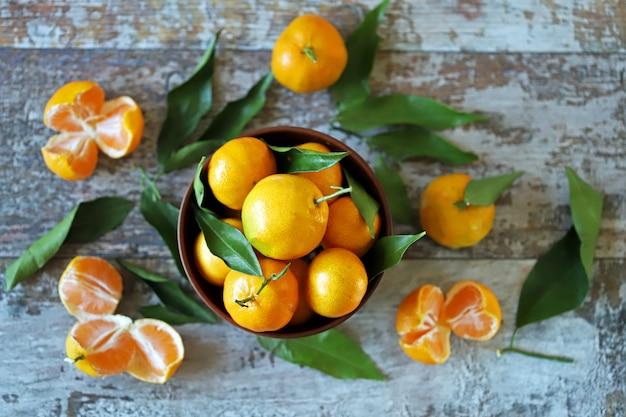 Tangerinas suculentas maduras em uma tigela. folhas de tangerina. mandarinas perfumadas frescas. colher tangerinas.