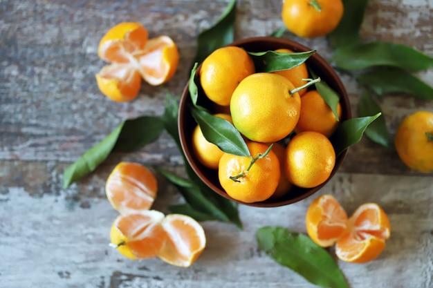 Tangerinas suculentas maduras em uma tigela. folhas de tangerina.