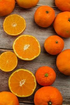 Tangerinas, tangerina descascada e fatias de tangerina sobre uma mesa de madeira branca. copie o espaço