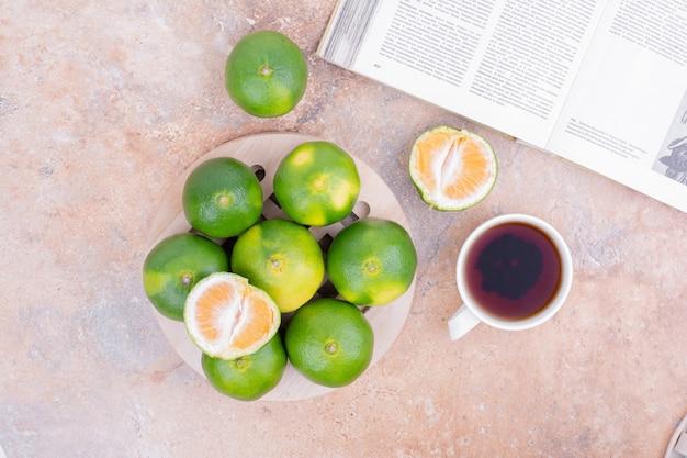 Tangerinas verdes com uma xícara de chá.