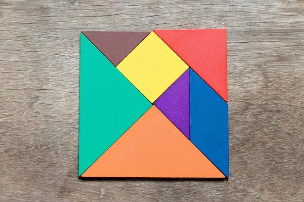 Tangram de cor em forma quadrada em fundo de madeira