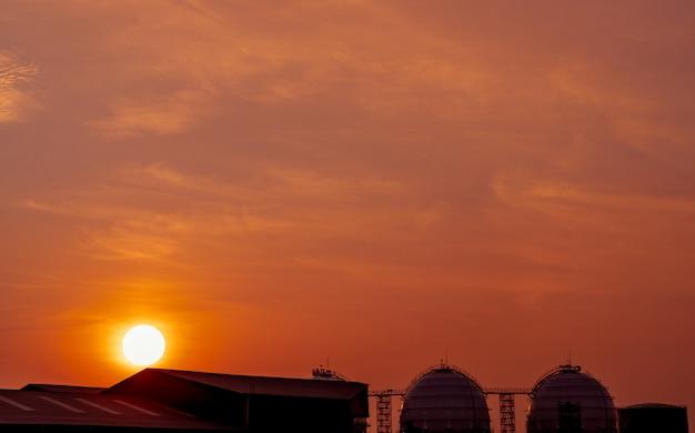 Tanque de armazenamento de gás industrial. tanque de armazenamento de gnl ou gás natural liquefeito. céu do sol vermelho e laranja. tanque de gás esférico na refinaria de petróleo. tanque de armazenamento acima do solo. indústria de armazenamento de gás natural.