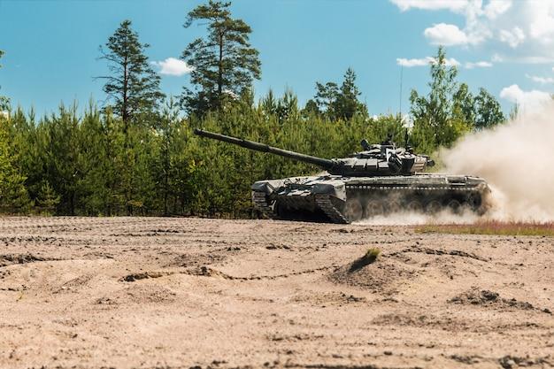 Tanque de batalha principal da rússia vai poeira em uma estrada florestal